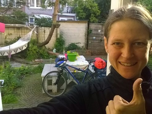 Me showing thumbs up with bike and garden in the background.